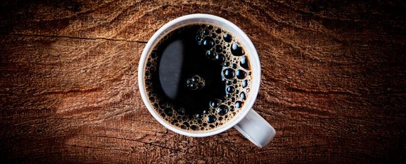 Svart kaffe på träbord